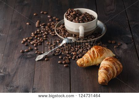 Fresh coffee beans on wood with croissant