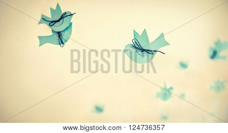 Abstract image of blue paper birds on pastel bacground