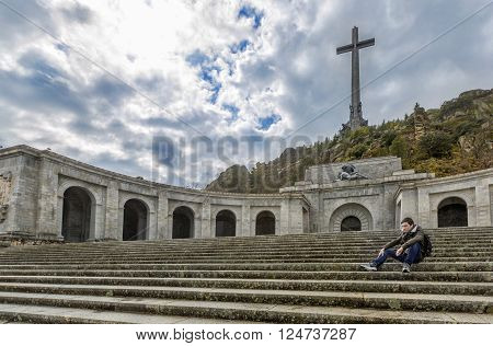 Young man is sitting sad and thoughtful on the stairs of Valley of the Fallen (Valle de los Caidos) Madrid Spain.