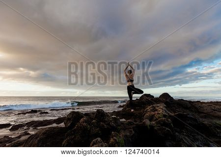 Summer sunrise yoga session on beautiful Playa de La Tejita beach with view on atlantic ocean and Punta Roja rock - tropical Tenerife island Canary in Spain. Vriksha-asana tree pose
