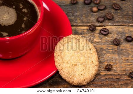 Coffee cup with biscuit on dark wooden table