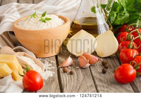 Raw rice and ingredients for cooking risotto. Rustic background. Horizontal permission. Selective focus.