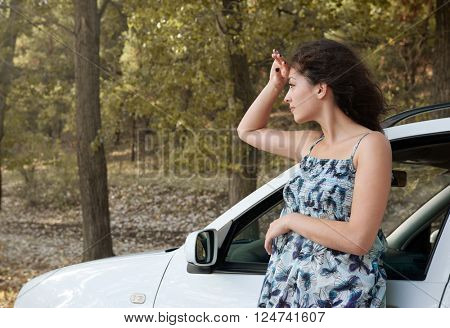 girl stand on country road near car look into the distance, big high trees, summer season, yellow toned