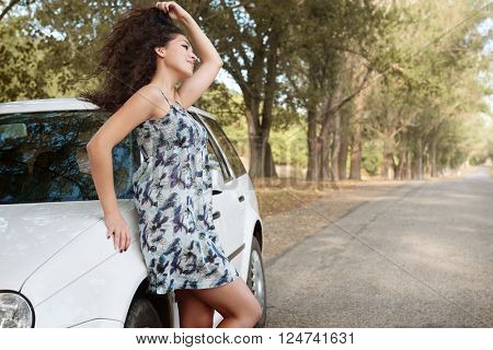 girl stand on country road near car, big high trees, summer season, yellow toned