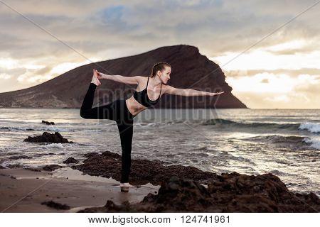 Summer sunrise yoga session on beautiful Playa de La Tejita beach with view on atlantic ocean and Punta Roja rock - tropical Tenerife island, Canary in Spain. Warrior pose - Virabhadrasana