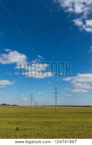 Electricity poles in the field with nice sky and clouds