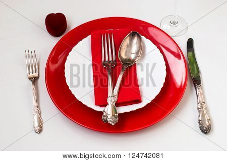 Serving holiday table spoon fork knife white and red plates and decor heart on a white table. dinner. holiday valentine