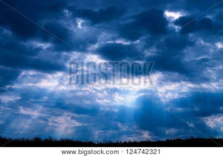 sunbeams through dark clouds on the ground