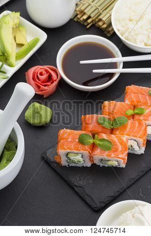 Sushi Roll With Fresh Ingredients With Ginger Wasabi Over Black Background
