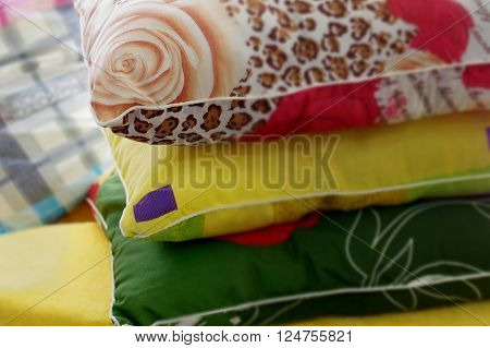 Pillows and pillowcases in various colors stacked cropped closeup with selective focus