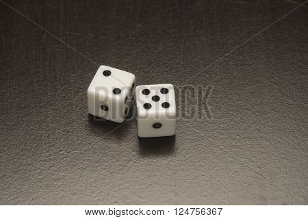 Pair of black and white gambling dice on a dark surface.