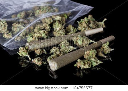 Pile of medical cannabis dried buds scattered from nylon package and two marijuana joints on black background from side