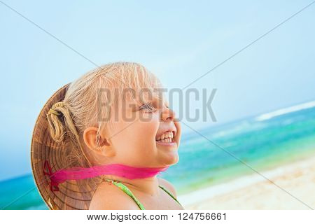 On sunny white sand beach happy smiling baby girl with vietnamese straw hat on head has fun before swimming in sea waves. Active travel family lifestyle water activity on summer vacation with child.