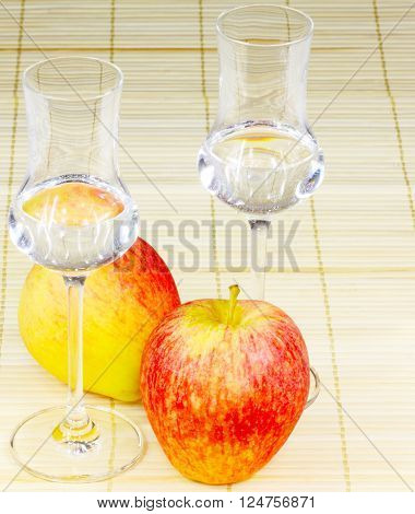 Two glasses of apple brandy with apples on reed mat