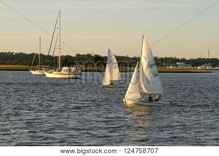 Wrightsville Beach North Carolina USA - November 13 2015: Sailboats sail on the scenic waters of the Atlantic Intracoastal Waterway off Wrightsville Beach NC around sunset