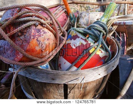 A bushel of colorful old crab pot buoys and boat ropes outside in the sunlight.