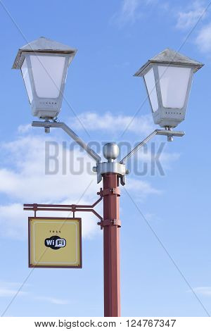 Free WiFi - wireless internet sign on the street lamppost on blue sky background