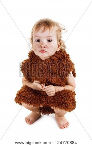 Little funny Neanderthal boy in a suit with a grubby face. Humorous concept ancient caveman. Isolated on white.