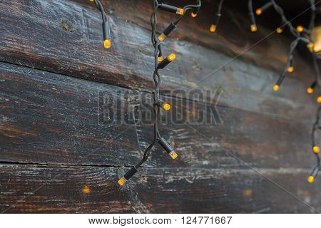 Luminous garlands on a wooden background. Decorate