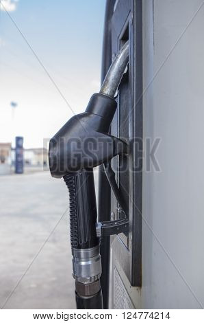 Closeup of a gas station handle nozzle over blue sky