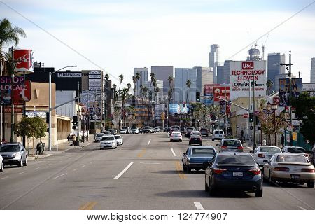 LOS ANGELES, UNITED STATES - DECEMBER 27: Road traffic on a main road in Koreatown in Los Angeles with views of the financial buildings and skyscrapers of the downtown on December 27, 2015 Los Angeles.