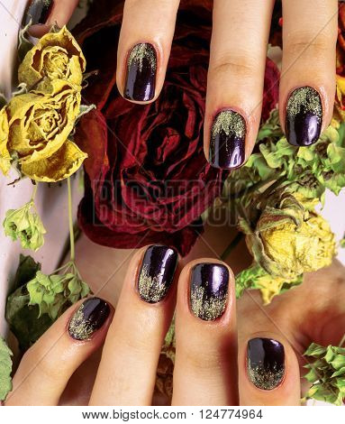 close up picture of manicure nails with dry flower red and yellow rose, dehydrated by winter close up
