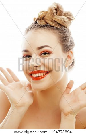 young blond woman with bright make up smiling pointing gesturing emotional isolated like doll lashes on white close up
