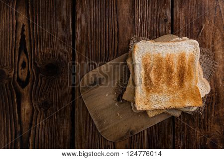 Toasted toast bread (selective focus) on vintage wooden background