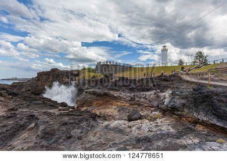 KIAMA, AUSTRALIA - MAR 30 2016: Kiama Lighthouse with water spraying out of the blowhole, Sydney, NSW, Australia