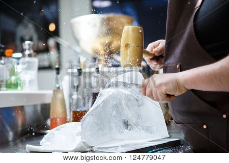 Bartender mannually crushed ice with wooden hammer and metal knife.