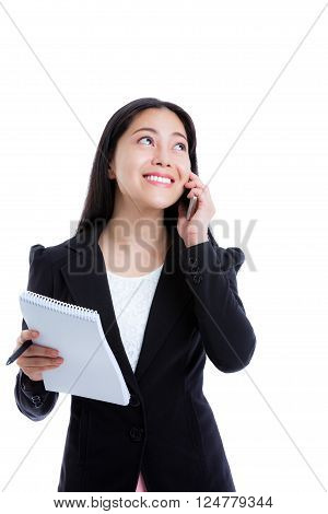 Young happy businesswoman talking on mobile phone and holding note paper. Isolated on white background. Positive human emotion. Studio shot.