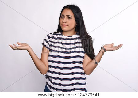 Indecisive young woman with arms open. Isolated white background.