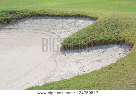 Heart shape sand bunker on the beautiful green golf course.