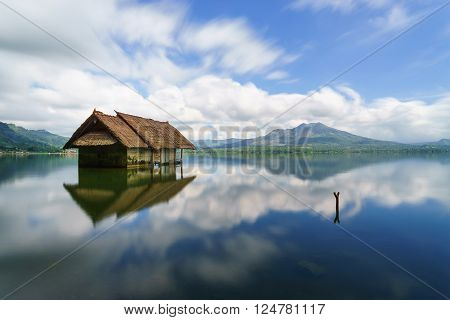 Lake Batur overlooking serene and beutiful Mount Batur during blue sky cloudy day with abandoned sub-merge house at foreground.