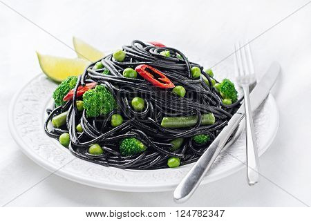 Spicy black spaghetti with green peas, green beans and broccoli on white plate, studio isolated, close up