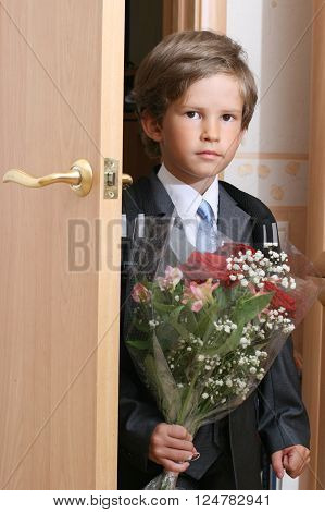 A first-grader with a bouquet at door