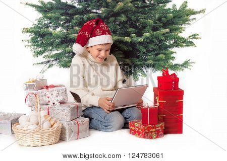 A boy sits with netbook and new year presents