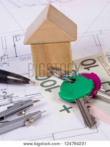 House shape made of wooden blocks, home keys, accessories for drawing and polish currency money on electrical construction drawings, concept of building house, drawing for projects