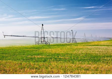 Agricultural irrigation system watering field on sunny day