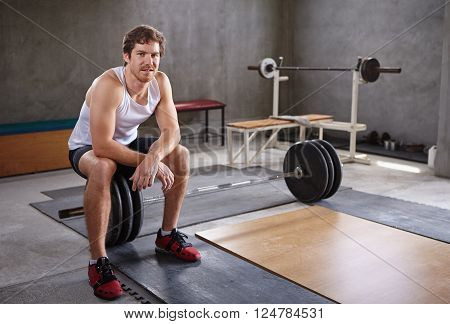 Handsome young man sitting on wieghts looking at the camera in a private gym