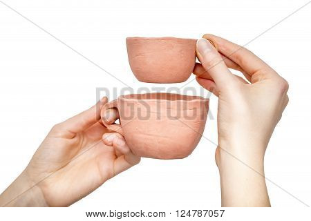 Close view of two clay cups in woman's hands isolated on white background