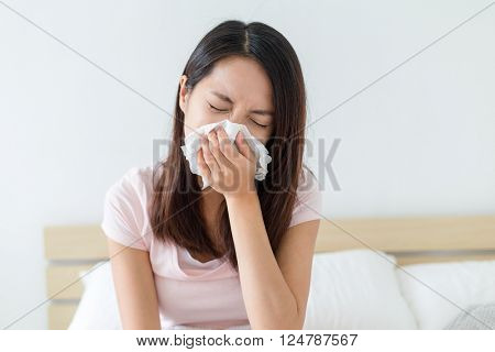 Woman got cold and sneeze on bed