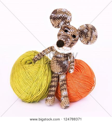small colorful knitted toy mouse in a white scarf playing with colored yarn threads of wool Bright children's toy clew