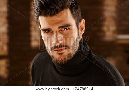 Closeup photo of handsome young man in turtleneck, looking at camera.