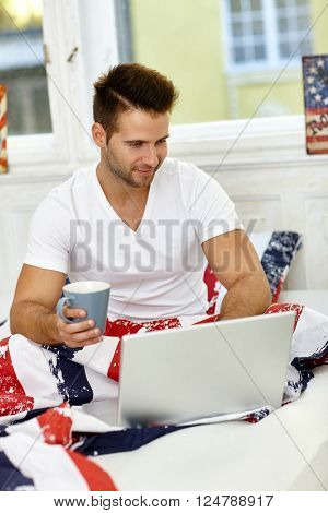 Young man drinking coffee, using laptop computer in the morning in bed.