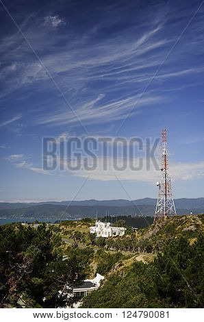Red and white tele-radio tower against a background of the blue sky.