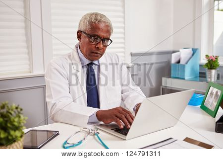 Senior black male doctor in white coat working in an office