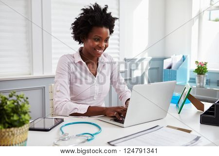 Black female doctor at work in office using laptop computer