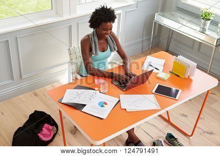 Woman using computer at home after exercising, elevated view