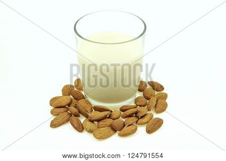 Heap of almonds and a glass of almond milk, on white background.